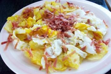 Tapa patatas fritas y huevos rotos con jamón